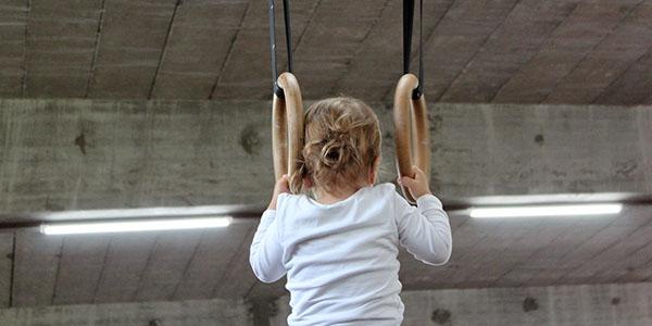 Niño realizando un ejercicio en anillas de gimnasia